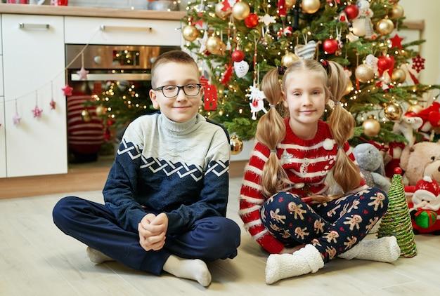 Fratello e sorella che si siedono vicino all'albero di natale