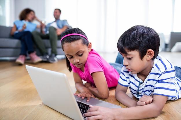 Fratello e sorella che si trovano sul pavimento e che per mezzo del computer portatile
