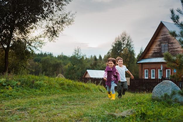 Fratello e sorella corrono per mano nella casa del villaggio. vacanze al villaggio con mia nonna.