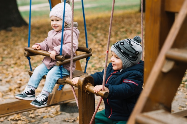 Fratello e sorella del bambino sul campo da giuoco di autunno