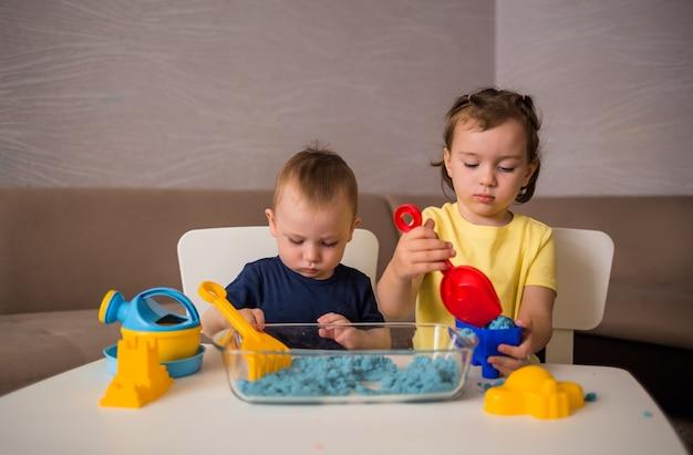 Fratello e sorella giocano con la sabbia al tavolo della stanza. giochi con sabbia cinetica.