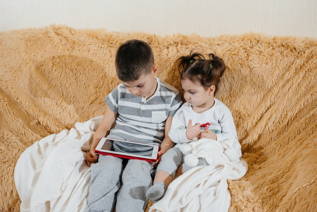 Fratello e sorella giocano sul divano del tablet