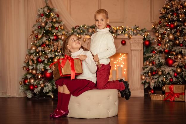Fratello e sorella happy gemini si scambiano un regalo di capodanno a casa vicino al camino e all'albero di capodanno