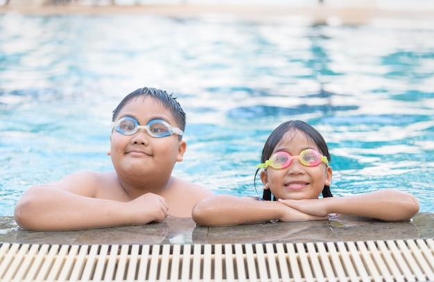 Fratello e sorella indossano occhiali e sorridono nel nuoto