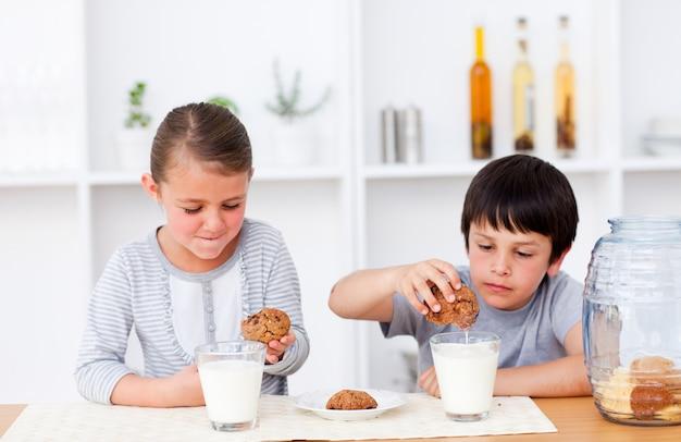 Fratello e sorella mangiando biscotti e bevendo latte