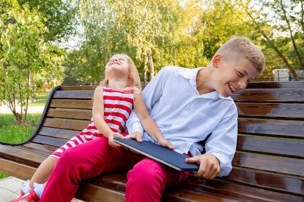 Fratello e sorella nel parco su una panchina si tolgono un computer portatile l'uno dall'altro