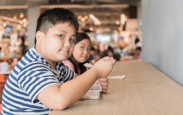 Fratello e sorella obesi che mangiano il pranzo della scatola nella corte dell'alimento, concetto di pasto rapido