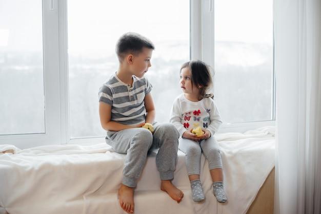 Fratello e sorella sono seduti sul davanzale a giocare e mangiare mele. felicità