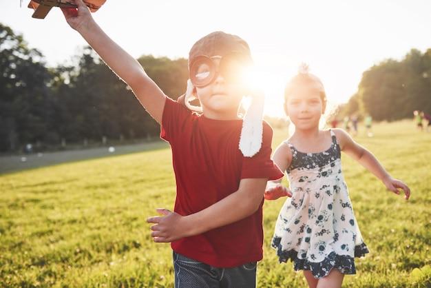 Fratello e sorella stanno giocando insieme. due bambini che giocano con un aeroplano di legno all'aperto