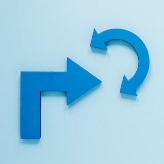 Frecce blu di disposizione piana su fondo blu