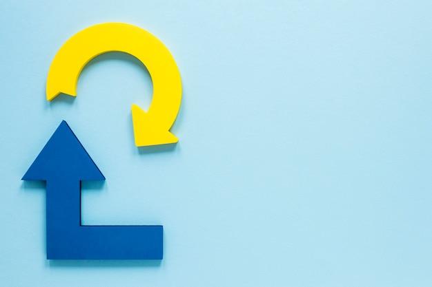 Frecce blu e gialle di disposizione piana su fondo blu con copia-spazio