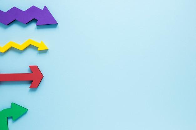 Frecce colorate laiche piane su sfondo blu con copia-spazio