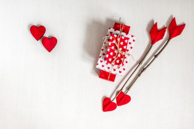 Frecce del ramoscello di giorno di biglietti di s. valentino su fondo di legno bianco con i contenitori di regalo ed i cuori rossi.