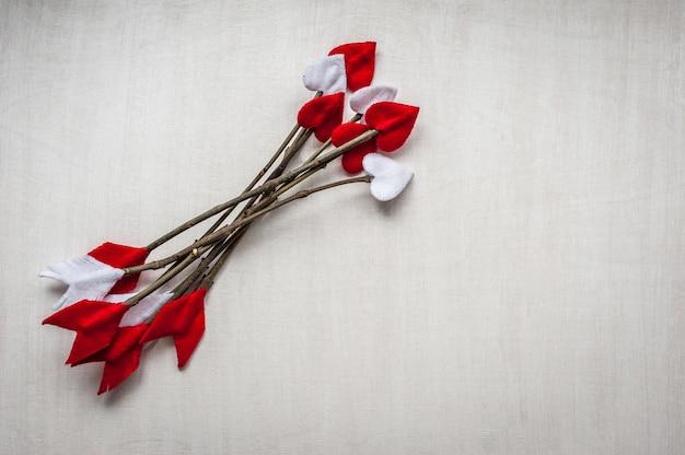 Frecce del ramoscello di giorno di biglietti di s. valentino su fondo di legno bianco. le frecce di cupido fatte a mano.