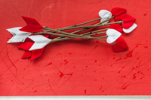 Frecce del ramoscello di giorno di biglietti di s. valentino su fondo di legno rosso. le frecce di cupido fatte a mano.