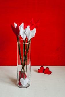 Frecce e cuori del ramoscello di giorno di biglietti di s. valentino su fondo di legno e sul vaso di vetro rossi.