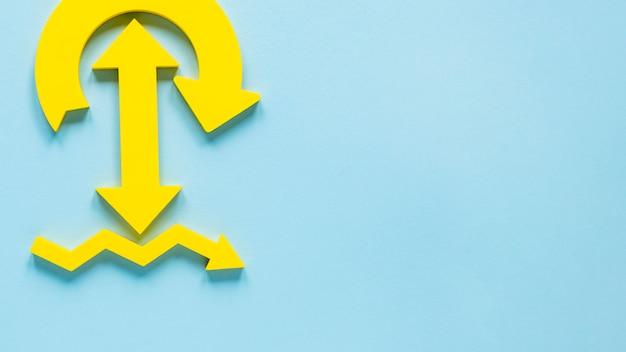 Frecce gialle di disposizione piana su fondo blu con lo spazio della copia