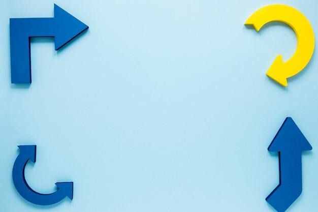 Frecce gialle e blu di disposizione piana su fondo blu con copia-spazio