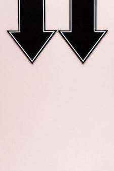 Frecce nere laiche piane rivolte verso il basso su sfondo rosa con copia-spazio
