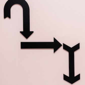 Frecce nere laiche piatte su sfondo rosa