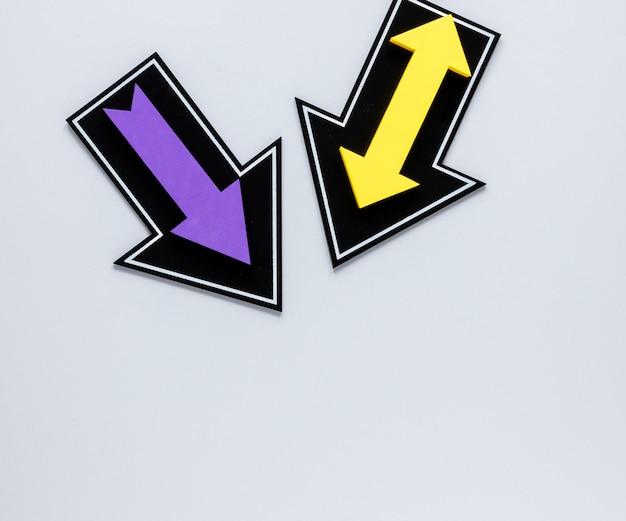 Frecce viola e gialle di disposizione piana su priorità bassa bianca