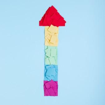 Freccia arcobaleno fatta di carte colorate