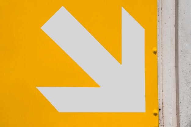 Freccia bianca del sottopassaggio su fondo giallo