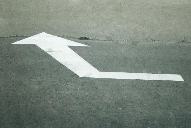 Freccia bianca di direzione sulla strada
