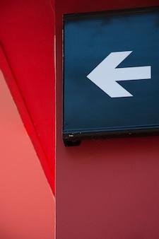 Freccia bianca moderna su edificio rosso