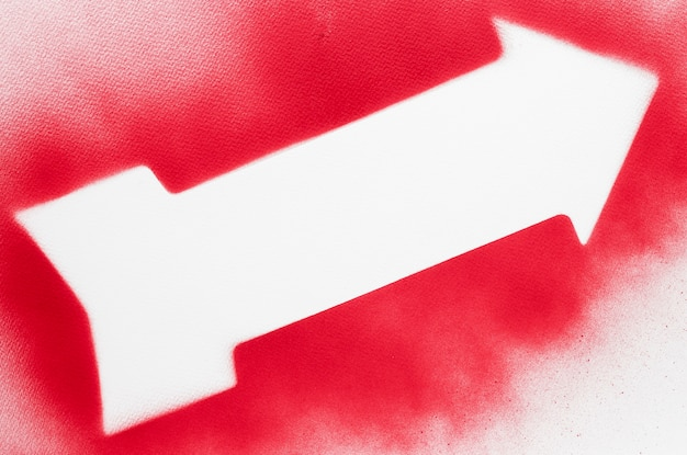 Freccia bianca vista dall'alto con contorno rosso spruzzato