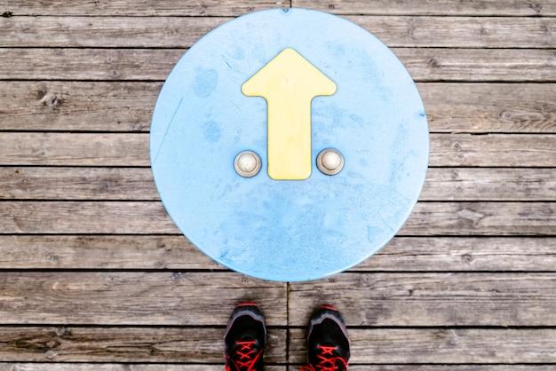 Freccia che indica la direzione con i piedi del viaggiatore su legno
