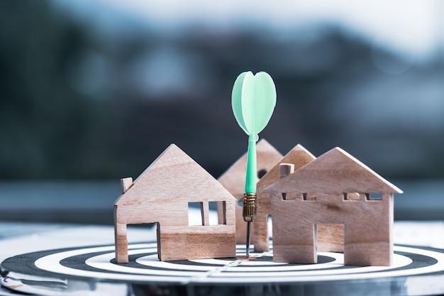 Freccia del dardo o bersaglio che colpisce sul centro di destinazione del numero con il modello di casa in legno in miniatura