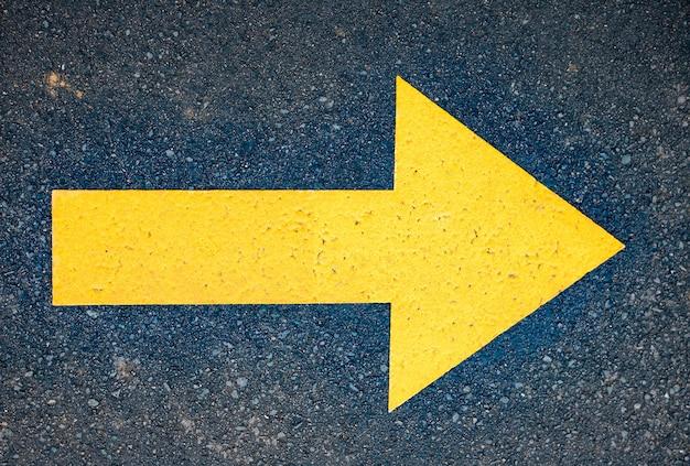 Freccia gialla dipinta in strada asfaltata. segnale di direzione per pellegrini in modo di san giacomo, camino de santiago de compostela, spagna