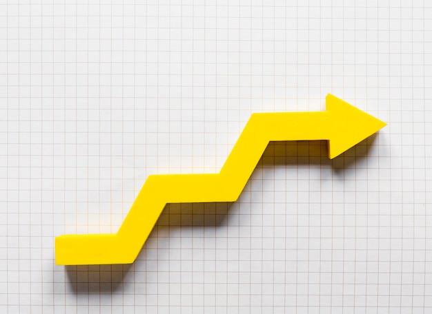 Freccia gialla piatta sul taccuino di matematica