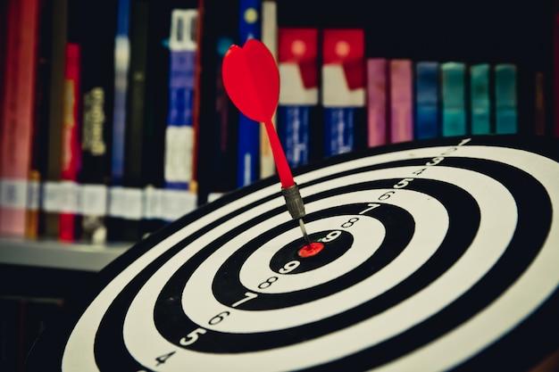 Freccia rossa del dardo che colpisce nel centro dell'obiettivo del bersaglio o del centro per il fuoco di affari, concetto.