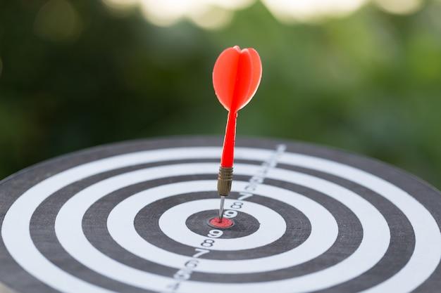 Freccia rossa dell'obiettivo del dardo che colpisce sul centro con, obiettivo di vendita e concetto di successo di affari