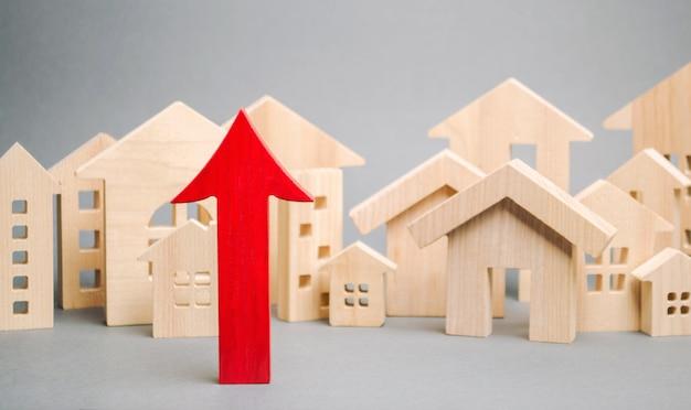 Freccia rossa su e case di legno in miniatura.
