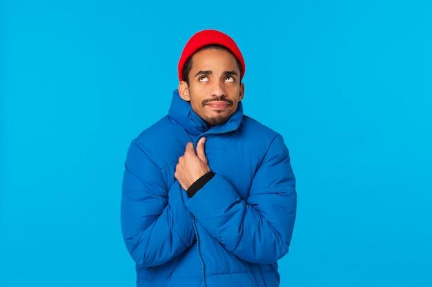 Freddo gelido, concetto di clima invernale. giovane studente maschio afroamericano infastidito e scontento in cappello rosso hipster, giacca imbottita, si avvolge stretto e guarda in alto, tremando da bassa temperatura