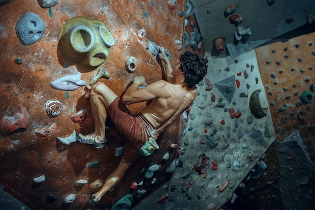 Free climber arrampicata su masso artificiale al chiuso