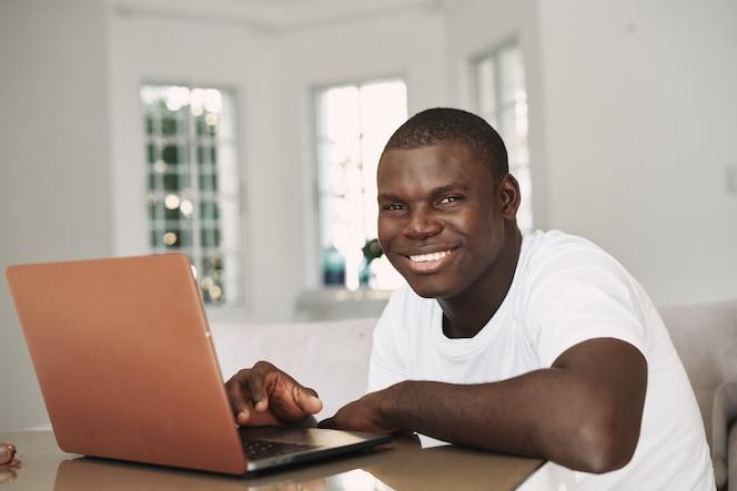 Free lance afroamericane maschii con il computer portatile a casa