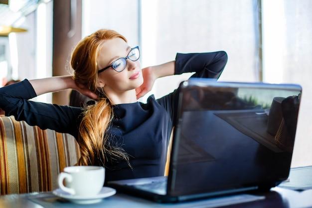 Free lance allegre splendide della donna con buon umore facendo uso del computer portatile