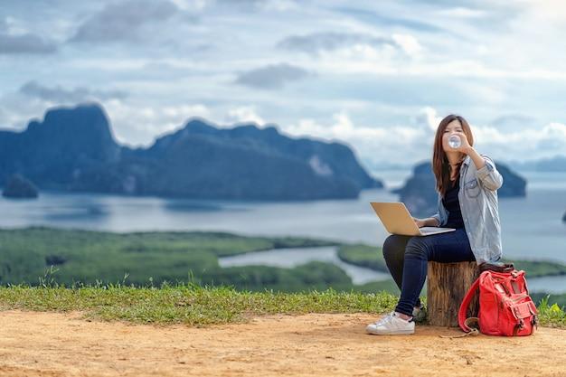 Free lance asiatiche della donna che lavorano con il computer portatile di tecnologia e che bevono l'acqua a fantastico