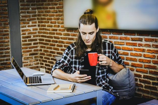 Free lance del giovane dei pantaloni a vita bassa facendo uso dello smart phone mobile e del computer portatile per lavorare nel workpl del caffè del sottotetto