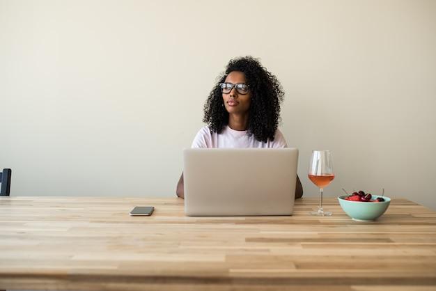 Free lance femminili afroamericane che per mezzo del computer portatile a casa