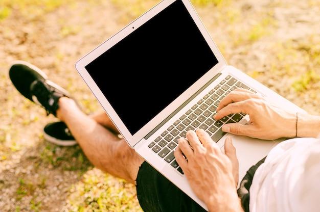 Free lance maschii che per mezzo del computer portatile mentre lavorando fuori