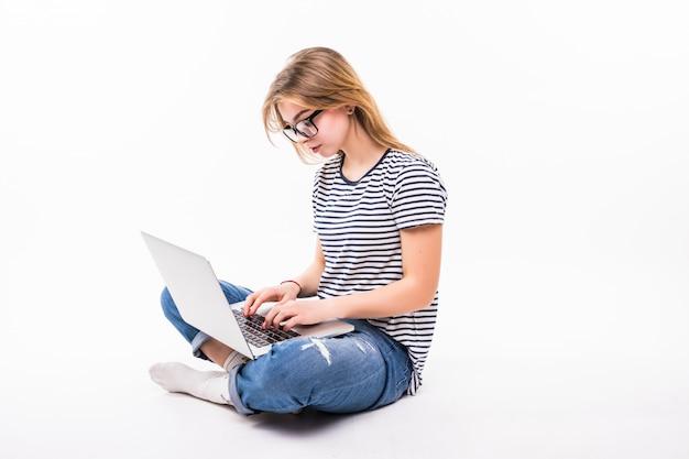 Freelance o lavoro a casa laptop. la bella donna in casuale si siede sul pavimento e lavora con il computer portatile con le gambe attraversate
