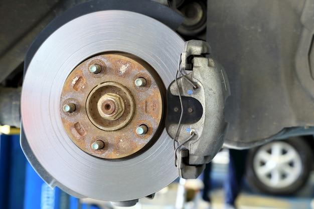 Freni a disco su auto in corso di sostituzione di pneumatici nuovi nel garage.