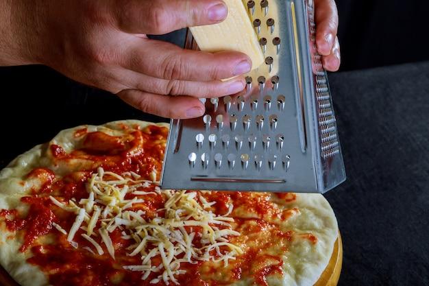 Fresca e originale pizza cruda italiana, preparazione in mani tradizionali di pizza da pizza su pi