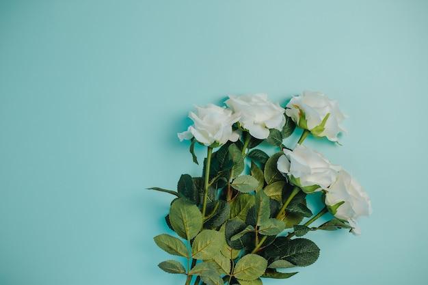 Freschezza primaverile rose bianche con foglie verdi. mazzo di belle rose bianche con gambo lungo e copia spazio.