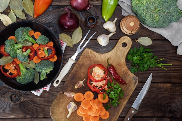 Freschi pezzi di carote, broccoli e peperoncino sul bordo della cucina in legno